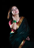 Indian mood. Sitting beautiful young woman posing in a sari dres Stock Images