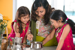 Indian mother cooking with her daughters. At kitchen Royalty Free Stock Images