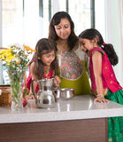 Indian mother cooking with her daughters. At kitchen Stock Images