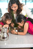 Indian mother cooking with her daughters. At kitchen Royalty Free Stock Image