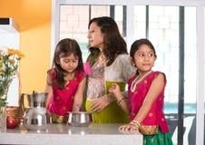 Indian mother cooking Stock Photos