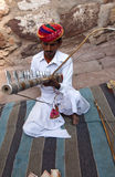 Indian musician. Rajasthani musician playing his music instrument sitting before a fort Stock Images