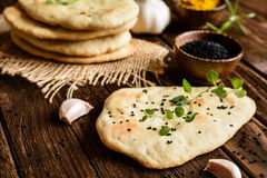 Indian Naan bread. Traditional Indian Naan bread with garlic on a wooden background Stock Photo
