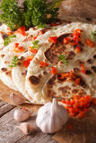 Indian Naan flat bread with garlic and pepper macro. vertical Stock Photos