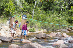 Indian native guides crossing river with traditional backpacks Royalty Free Stock Photo