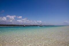 Indian ocean beach paradise. Sailing boats in ocean near white sand beach with blue sky. Diani beach Kenya Stock Photos
