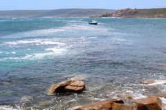 Indian Ocean at Canal Rocks West Australia. A lone fishing boat lies anchored in the Indian Ocean at Canal Rocks south western Australia  on a calm summer Royalty Free Stock Photography