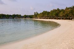 Indian ocean coastline on Maldives island. Beach chairs under straw umbrellas. White sandy beach and calm sea. Bungalows. On background Travel and vacation stock images
