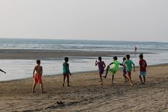 Indian Ocean in Goa. Рeople have a rest in the evening. Indian Ocean in Goa. Evening and sunset. Morjim beach. Sand and silence. А real pleasure of stock photos
