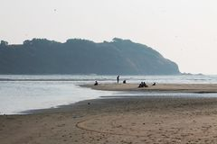 Indian Ocean in Goa. Рeople have a rest in the evening. Indian Ocean in Goa. Evening and sunset. Morjim beach. Sand and silence. А real pleasure of royalty free stock photos