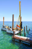 Indian Ocean Pile Drivers: Construction. BUSSELTON,WA,AUSTRALIA-JANUARY 15,2016: Workers and construction equipment platform with pile drivers in the Indian Royalty Free Stock Images