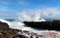 Indian Ocean waves dumping against dark basalt rocks on Ocean Beach Bunbury Western Australia. The mighty Indian Ocean waves dumping against dark basalt rocks stock images