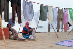 Indian old family sit near clothesline on ghat near sacred river Ganges in Varanasi Royalty Free Stock Images