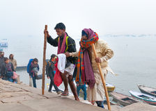 Indian old man with his son go on steps of Ghats in Varanasi Royalty Free Stock Photos