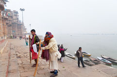 Indian old man with his son go on steps of Ghats in Varanasi Stock Images