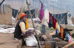 Indian old man sits near clothesline on ghat near sacred river Ganges in Varanasi Royalty Free Stock Photo