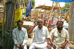 Indian old men talking on his mobile phone at a roadside shop. Royalty Free Stock Images