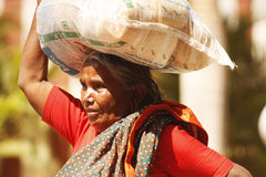 Indian old woman. Old woman with bag on her head Royalty Free Stock Photography
