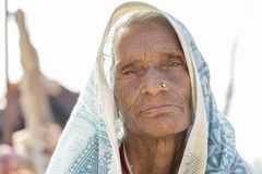 Indian old woman sits on the ghat near the Ganges river in the holy city of Rishikesh, India, close up royalty free stock images