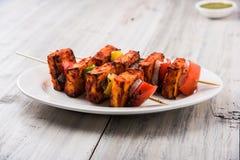 Indian paneer barbecue or tikka. Paneer Tikka Kabab - Tandoori Indian cheese skewers, malai paneer tikka / malai paneer kabab, chilli paneer served in white Stock Images