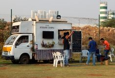 Indian people buy street food at food trucks stationed in open area Stock Images