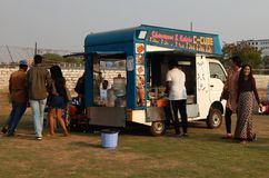 Indian people buy street food at food trucks stationed in open area Royalty Free Stock Photography