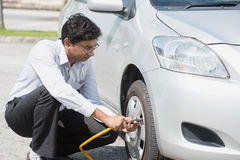 Indian people filling air to the car tires. Royalty Free Stock Photo