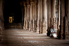 Indian people pilgrim resting inside ancient colonnade of Meenakshi Temple Stock Images