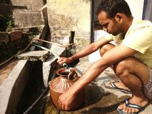 Indian people taking water from a source Stock Images