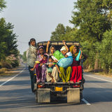 Indian people travelling on the overloades platform of a pickup truck Stock Photo