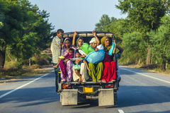 Indian people travelling on the overloades platform of a pickup truck Royalty Free Stock Image