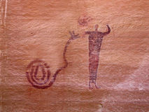 Indian Petroglyph. Of man and snake on red rock Stock Photo