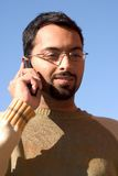 Indian on the phone. Young Indian guy talking on the phone Royalty Free Stock Photo