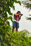 Indian photographer taking pictures in forest. Indian taking pictures in green mountain forest Stock Image