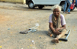 Indian physically challenged senior woman sit and beg or seek help on a busy road Stock Photos