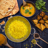 Indian pilau rice in balti dish served with chicken tikka masala. Curry, plain naan bread, vegetable samosas, and onion bhajis Stock Photos