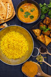 Indian pilau rice in balti dish served with chicken tikka masala. Curry, plain naan bread, vegetable samosas, and onion bhajis Stock Images