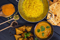 Indian pilau rice in balti dish served with chicken tikka masala. Curry, plain naan bread, vegetable samosas, and onion bhajis Stock Photo