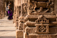 Indian pillar architecture woman in background. Stock Image