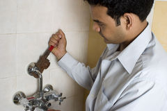 Indian plumber working on tap. Young Indian plumber repairing a tap with wrench Royalty Free Stock Photos