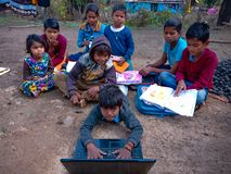 indian poor boy operating laptop computer system in unique posture open class in india January 2020