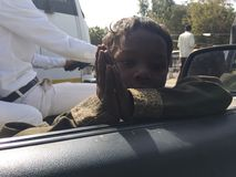 Indian poor child pray to car inside people say please give me money Stock Images