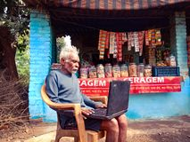 indian poor old man operating laptop computer system at grocery store in india January 2020