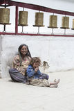 Indian poor woman with children begs for money from a passerby on the street in Leh, India Royalty Free Stock Photo