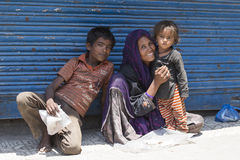 Indian poor woman with children begs for money from a passerby on the street in Srinagar, India Royalty Free Stock Photo