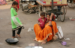 Indian poor woman with her children sell metal pans Royalty Free Stock Photography
