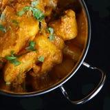 Indian Potato Curry. Bombay Aloo potato curry on black Stock Photos