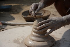 An Indian potter makes earthen lamps or 'diyas' ahead of the forthcoming Diwali festival Royalty Free Stock Photos