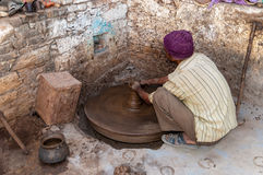 An Indian potter molds a clay pot Stock Images