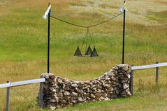 Indian Property. Part or a stone, wood & wire fencing hangs an iron TeePee symbol marking indian territory Royalty Free Stock Image